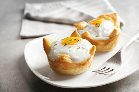 Tasty baked eggs in dough on plate