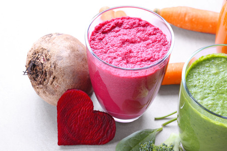 Fresh vegetable juices in glasses and heart made from beet on table Stockfoto