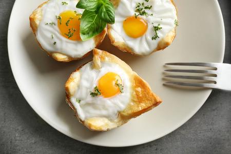 Tasty baked eggs in dough on plate