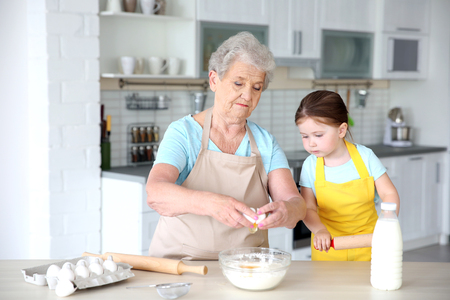 Cute little girl and her grandmother cooking on kitchen Imagens