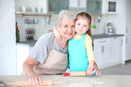 Cute little girl and her grandmother cooking on kitchen Banque d'images