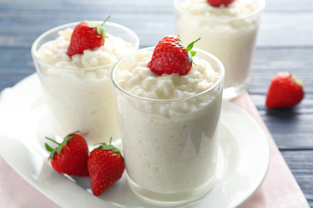 Creamy rice pudding with strawberry in glasses on table Stock Photo