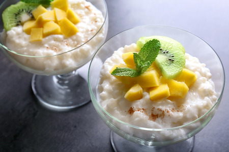 Creamy rice pudding with fruits in dessert bowls on table