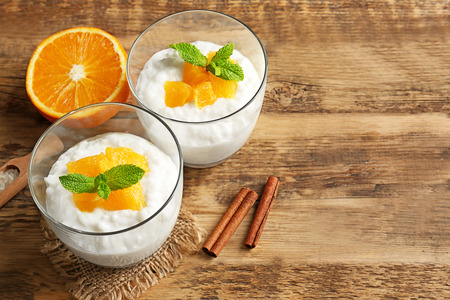 Creamy rice pudding with orange in glasses on wooden table