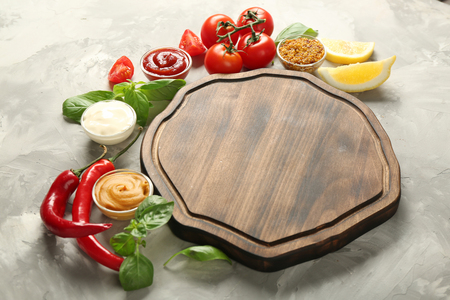 Wooden plate, different sauces and vegetables on grunge background