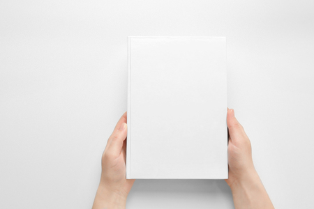 Female hands holding closed book with blank cover on light background