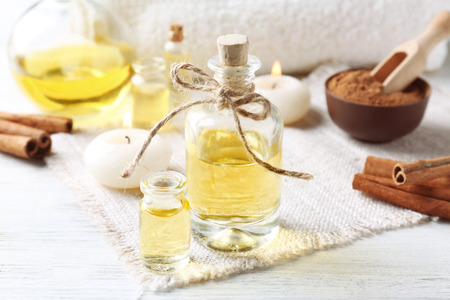 Composition with bottles of cinnamon oil on wooden background Stock Photo