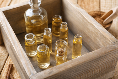 Bottles of cinnamon oil in box on wooden background