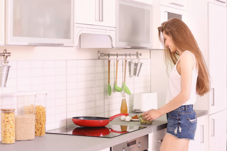 Morning of beautiful young woman preparing breakfast in kitchen