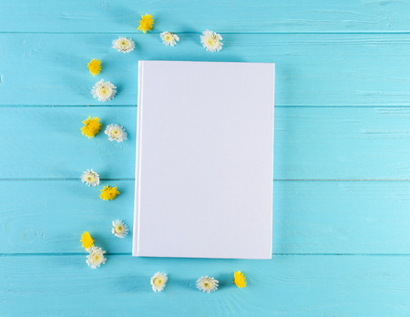 Book with blank white cover and beautiful flowers on color wooden background