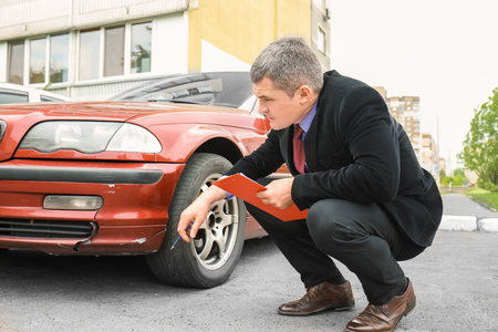 Insurance man checking broken car after accident Reklamní fotografie