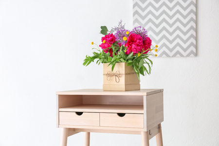 Gift box with beautiful floral composition of different fragrant flowers on table in light room Stockfoto