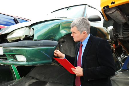 Insurance man checking broken car after accident