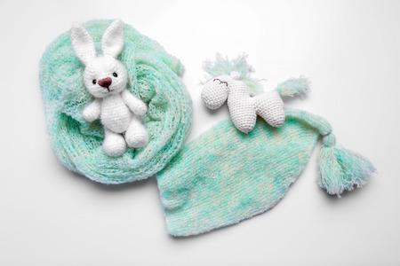 Juguetes tejidos a mano con ropa de bebé aislado en blanco Foto de archivo