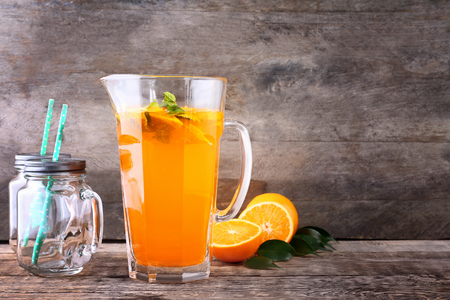 Jug of fresh orange lemonade on wooden background