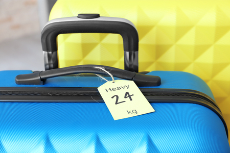 Tag on heavy suitcase. Luggage overweight concept Stock Photo