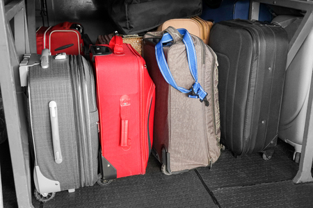 Different suitcases in luggage bay