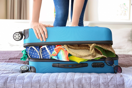 Woman trying to lock heavy suitcase on bed. Luggage overweight concept