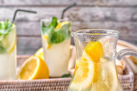 Jug of fresh lemonade on blurred background, close up Stock Photo
