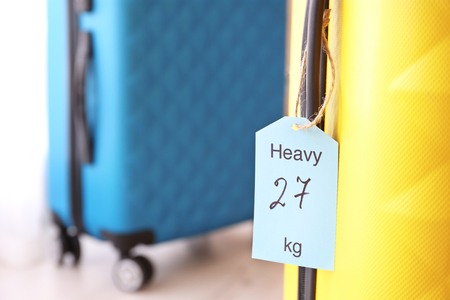 Tag on heavy suitcase. Luggage overweight concept 免版税图像