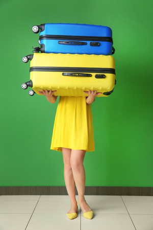 Young woman with suitcases near color wall. Luggage overweight concept