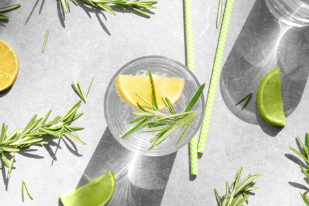 Glass of fresh lemonade with rosemary on grey background