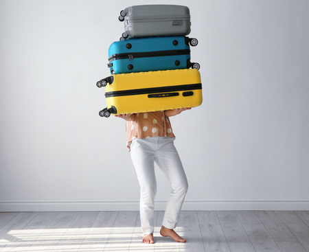 Young woman with suitcases in room. Luggage overweight concept