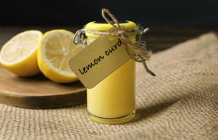 Glass jar with delicious lemon curd on table Imagens
