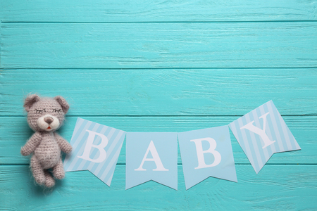 Knitted toy and word BABY on wooden background