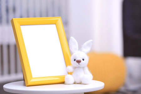 Empty photo frame with toy on table in baby room