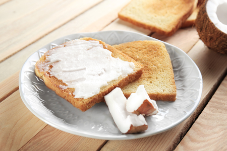 Delicious toasts with coconut oil in plate on wooden table Stock fotó