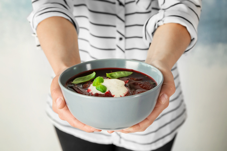 Woman holding bowl with beet soup on light background