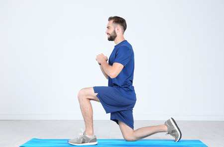 Sporty young man training legs on mat in gym