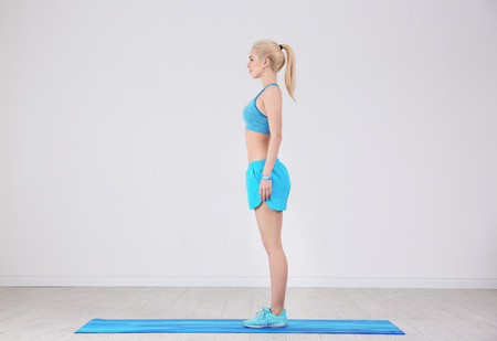 Sporty young woman standing on mat in gym