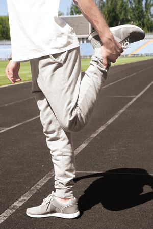 Sporty young man doing sport exercises for legs at stadium Stock Photo