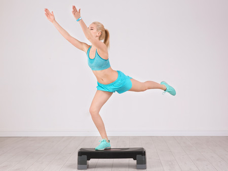 Young sporty woman training legs with stepper in gym 写真素材