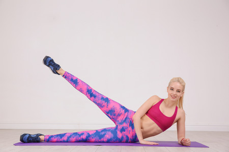 Sporty young woman training legs on mat in gym