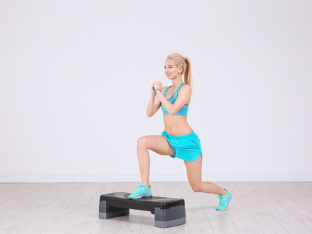 Young sporty woman training legs with stepper in gym Stock Photo