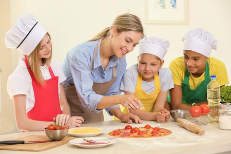 Grupa dzieci i nauczyciel w kuchni podczas lekcji gotowania
