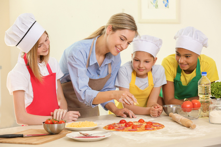 Gruppo di bambini e insegnante in cucina durante i corsi di cucina