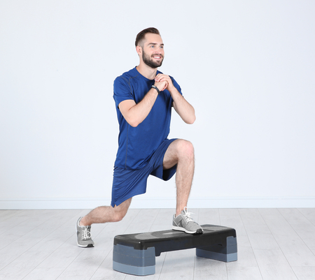 Young sporty man training legs with stepper in gym Stock Photo