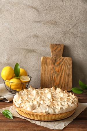Composition with tasty lemon meringue pie on wooden table