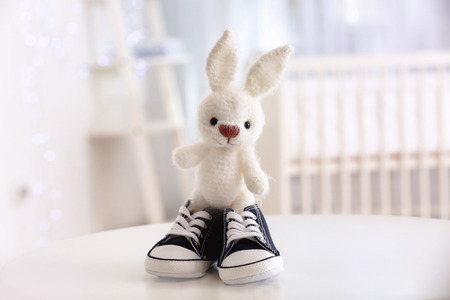 Cute knitted toy bunny and baby shoes on table 写真素材
