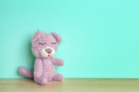 Cute knitted toy bear on color background