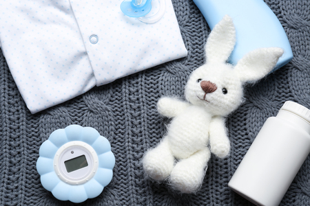 Cute baby accessories on gray knitted background