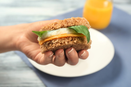 Woman holding sandwich with over easy egg and cheese in kitchen