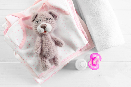 Knitted toy bear, baby clothes and accessories on table