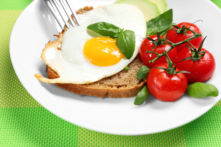 Delicious over easy egg with avocado, tomatoes and bread on kitchen table