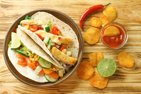Tasty fish tacos on plate with sauce and chips on wooden background
