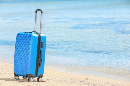 Packed suitcase at sea shore. Vacation concept